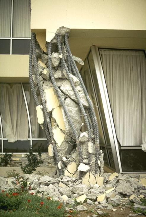 Pilar de uma estrutura de concreto armado se rompendo.